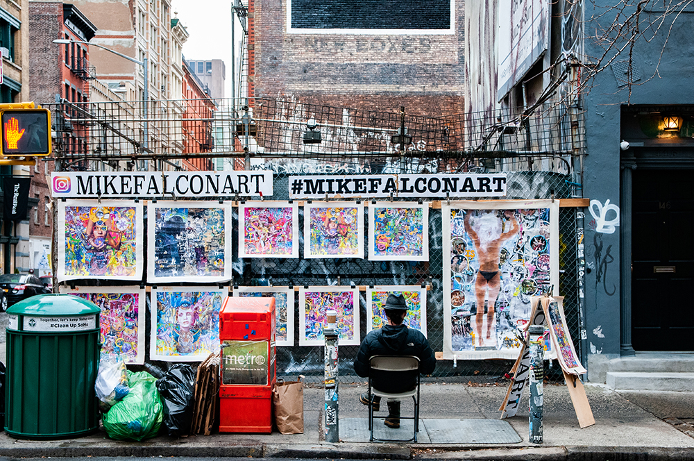Artist selling is art in a street of New York. 2018